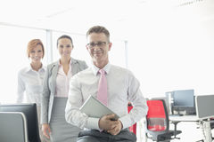 Portrait of happy businessman holding tablet PC with female colleagues in background at office Royalty Free Stock Photography