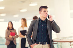 Portrait of happy businessman in office using phone. Royalty Free Stock Photos