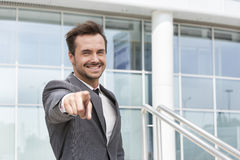 Portrait of happy businessman pointing at you outside office building Royalty Free Stock Image