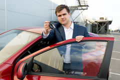 Portrait of happy businessman posing at car with keys Royalty Free Stock Images