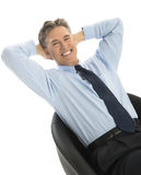 Portrait Of Happy Businessman Relaxing On Office Chair. Portrait of happy mature businessman relaxing on office chair against white background Royalty Free Stock Photo