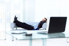Portrait of happy businessman relaxing in office. Portrait of happy businessman relaxing in white office Royalty Free Stock Photo