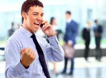 Portrait of happy businessman talking on mobile in office lounge. Royalty Free Stock Images