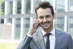 Portrait of happy businessman using cell phone outside office Stock Photo