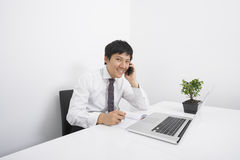 Portrait of happy businessman using cell phone while working at office desk Stock Images