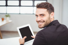 Portrait of happy businessman using digital tablet. Close-up portrait of happy businessman using digital tablet while sitting at desk in office Stock Image