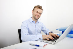 Portrait of happy businessman using laptop at desk in office Royalty Free Stock Photo