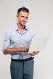 Portrait of a happy businessman using laptop Stock Photo