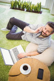 Portrait of happy businessman using laptop and mobile phone at creative office Royalty Free Stock Photos