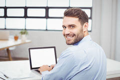 Portrait of happy businessman using laptop in office Stock Photography