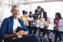 Portrait of happy businessman using mobile phone with team working in background Stock Photos