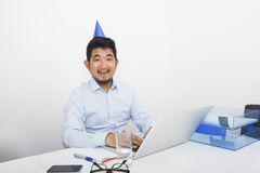 Portrait of happy businessman wearing party hat sitting at desk in office Stock Photography