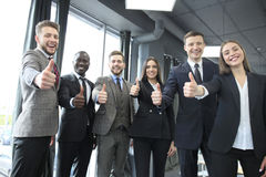 Portrait of happy businesspeople standing in office showing thumb up. Stock Image