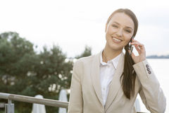 Portrait of happy businesswoman answering cell phone outdoors Stock Photo