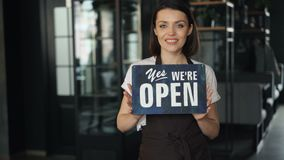 Portrait of happy businesswoman in apron holding open sign standing in new cafe. Smiling looking at camera welcoming customers. Business and people concept stock video
