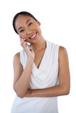 Portrait of happy businesswoman with head cocked using mobile phone. While standing against white background Royalty Free Stock Photography