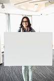 Portrait of happy businesswoman holding blank sign in creative office Royalty Free Stock Photography