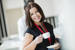Portrait of happy businesswoman holding coffee cup in seminar hall Stock Photo