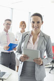 Portrait of happy businesswoman holding digital tablet with colleagues in background at office Royalty Free Stock Photography