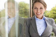 Portrait of happy businesswoman leaning on glass door Stock Photo