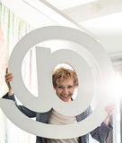 Portrait of happy businesswoman looking through at sign in creative office Stock Photography