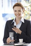 Portrait of happy businesswoman with mobile. Portrait of happy young businesswoman using mobilephone, drinking water and coffee Royalty Free Stock Photography