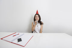 Portrait of happy businesswoman in party hat blowing horn at desk in office Royalty Free Stock Photos