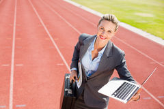 Portrait of happy businesswoman ready to run with a laptop and briefcase. On running track Stock Photography