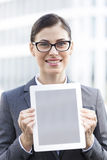 Portrait of happy businesswoman showing digital tablet outdoors Royalty Free Stock Image