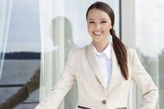 Portrait of happy businesswoman standing against glass door Royalty Free Stock Image