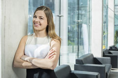 Portrait of happy businesswoman standing arms crossed at office lobby Royalty Free Stock Photo