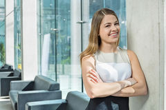 Portrait of happy businesswoman standing arms crossed at office lobby Royalty Free Stock Image