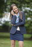 Portrait of happy businesswoman using cell phone at park Stock Photography