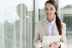 Portrait of happy businesswoman using digital tablet by glass door Royalty Free Stock Photo