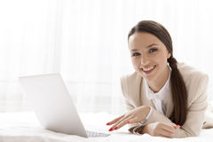 Portrait of happy businesswoman using laptop in hotel room Royalty Free Stock Photo