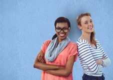 Portrait of happy businesswomen standing arms crossed against blue background Royalty Free Stock Image