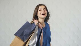 Portrait of Happy Buyer. Portrait of a happy buyer holding lots of shopping bags in the white background, indoor isolated shot stock footage