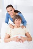 Portrait of happy caregiver with senior woman Stock Photos