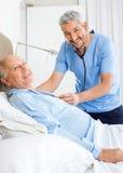 Portrait Of Happy Caretaker Examining Senior Man Stock Photography