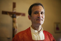 Portrait of happy catholic priest smiling at camera in church. Man and faith, portrait of catholic priest on altar in church looking at camera and smiling Royalty Free Stock Image