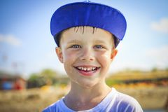 Portrait of happy caucasian boy in cap with wet drops on his face. The face of smiling boy after bathing Stock Photos