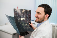 Portrait of a happy caucasian male radiologist holding x-ray while sitting at his office Stock Photography