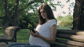 Pregnant Woman Sits On A Park Bench On A Summer Day And Uses A Smartphone Apps. Portrait of a happy caucasian pregnant brunette woman sitting on a park bench on stock video