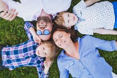 Portrait of happy caucasian smiling family lying down on the grass. Portrait of happy caucasian smiling family with two kids lying on the grass, top view Stock Image