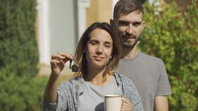 Portrait happy caucasian woman with the cup of tea and handsome man standing in front of large house. Girl showinghouse