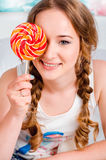 Portrait of a happy, cheerful, blonde young girl is holding a bi. G round lollipop and closes one eye and he smiles. Fun. Children. Rodrostki Stock Photos