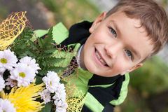 Portrait of happy cheerful boy with flowers Stock Photography