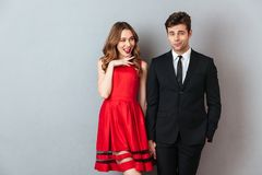 Portrait of a happy cheerful couple dressed in formal wear. Standing while holding hands other over gray wall background Stock Photos