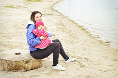 Portrait of happy cheerful family resting on the beach. Laughing faces, mother holding adorable child baby girl and hugging. Mom and daughter outdoors in royalty free stock image