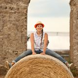 Portrait of happy cheerful teen sitting on haystack Royalty Free Stock Photo